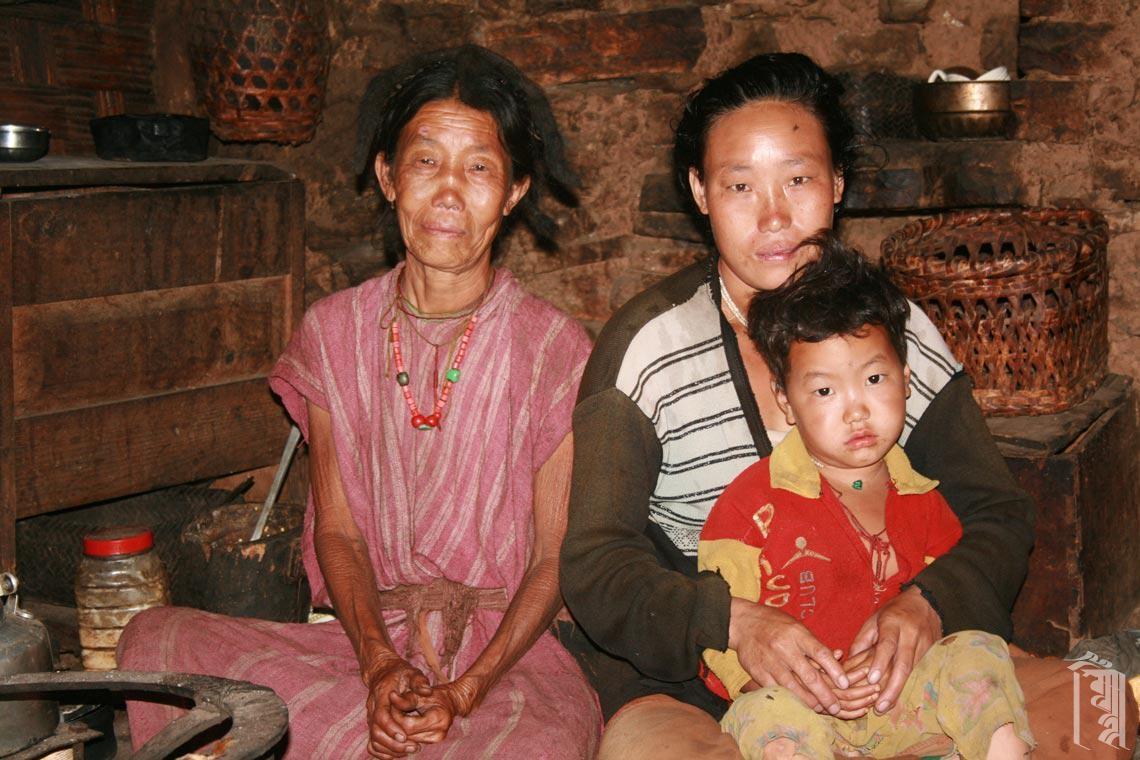Eine kleine Familie in ihrem Haus in einem Monpa-Dorf im Nordosten Indiens.