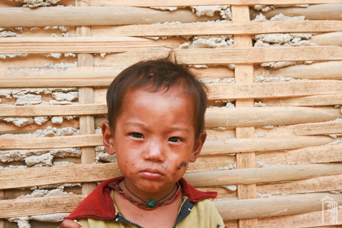 Kleinkind an einer Bambuswand