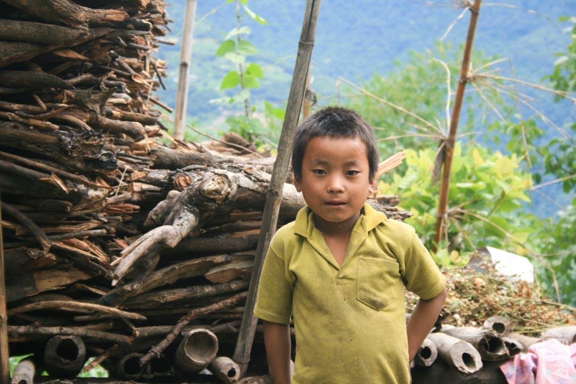 Kind bei einem Holzstapel