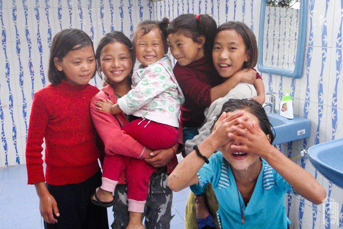 Eine Gruppe von Mädchen probiert die neuen Waschbecken am Gemeinschaftsbadehaus aus.