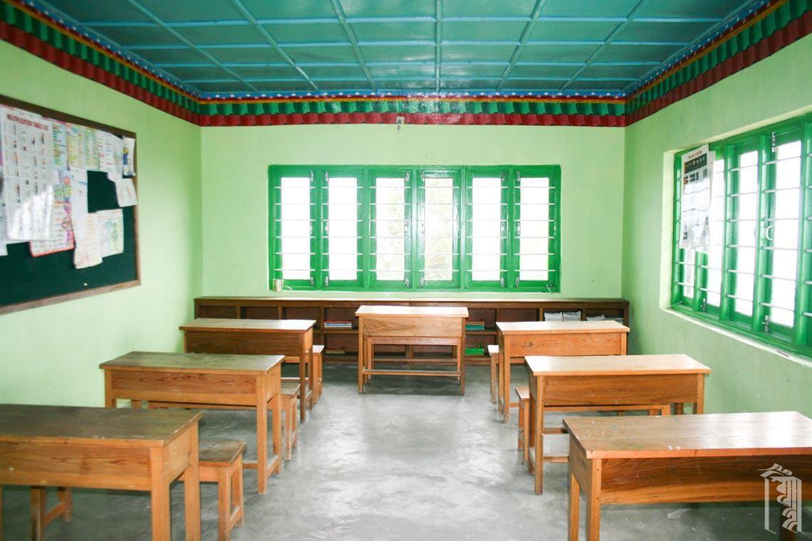 Die Schreibtische reihen sich ordentlich in einem Jhamtse Gatsal Klassenzimmer aneinander.