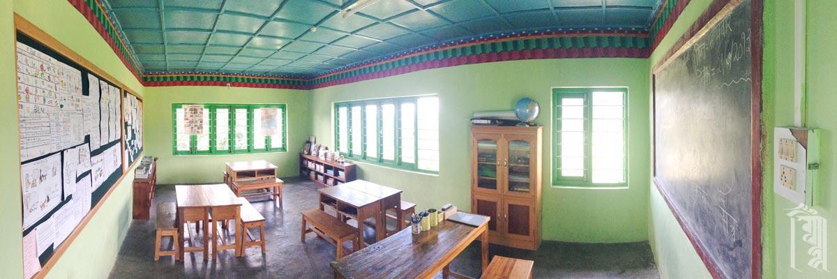 Eines der Klassenzimmer am Ende eines Gebäudes, mit vielen lichtdurchfluteten Fenstern.