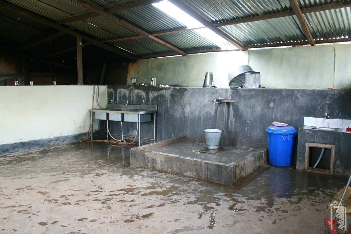 Eine große offene Fläche mit Spülbecken, Wasserhähnen, Mülleimern und Trockengestellen ermöglicht es jedem, beim Abwaschen nach den Mahlzeiten zu helfen.