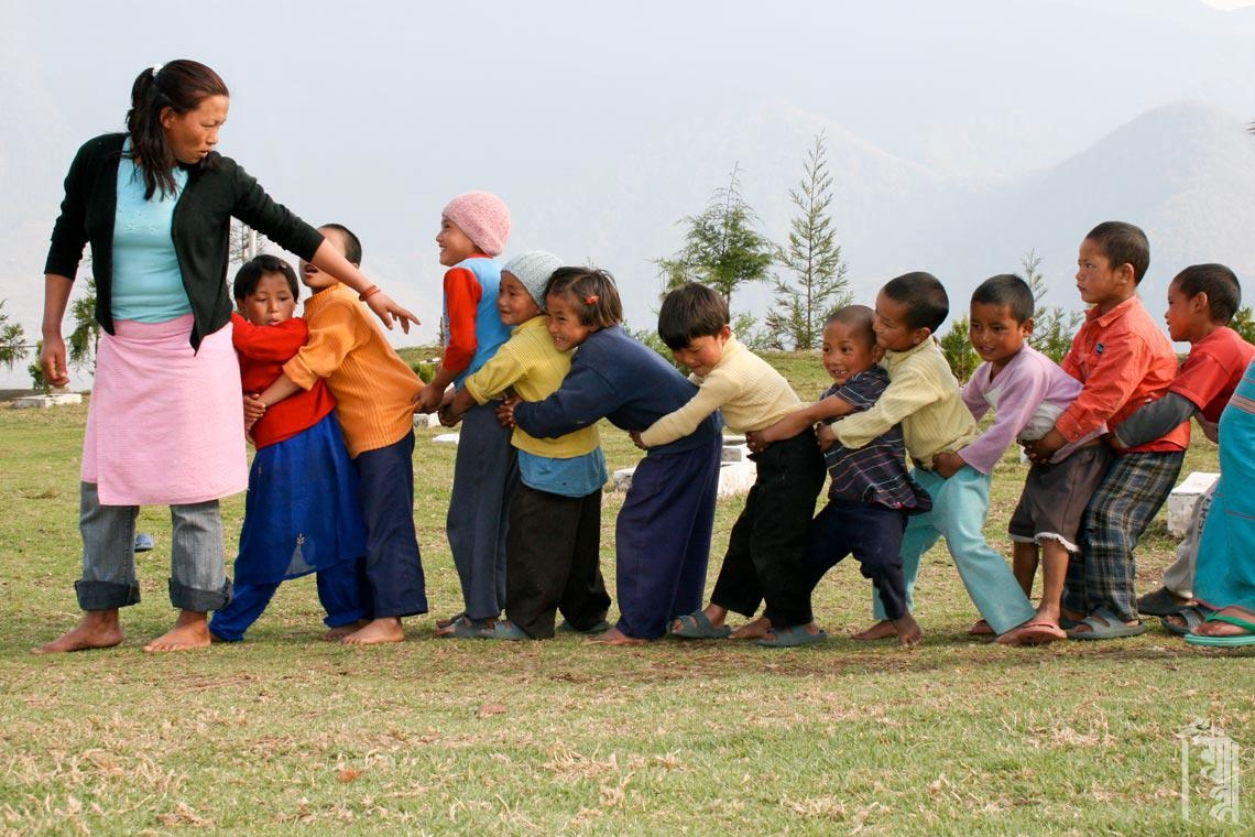 Eine Hausmutter mit einer Gruppe von Kindern beim Spielen auf dem Schulgelände.