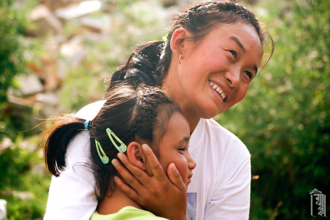 Ama la Yangzom verbringt die Zeit mit einem der Kinder an einem warmen Frühlingstag.