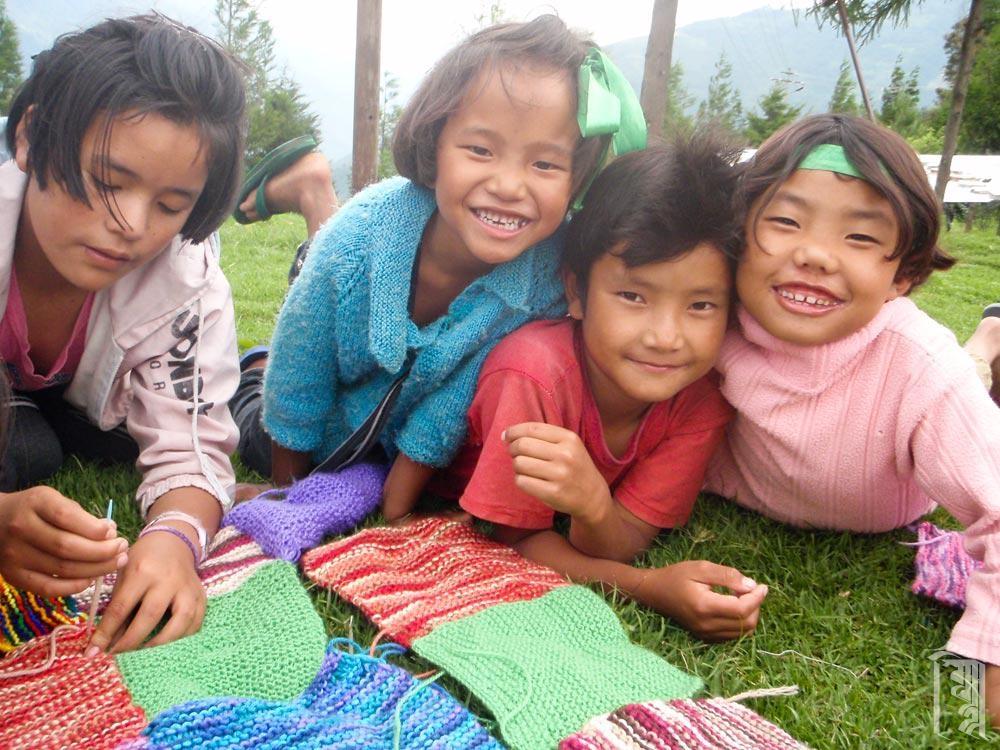 Einige der Kinder arbeiten in ihrer Freizeit gemeinsam an einem Strickprojekt.