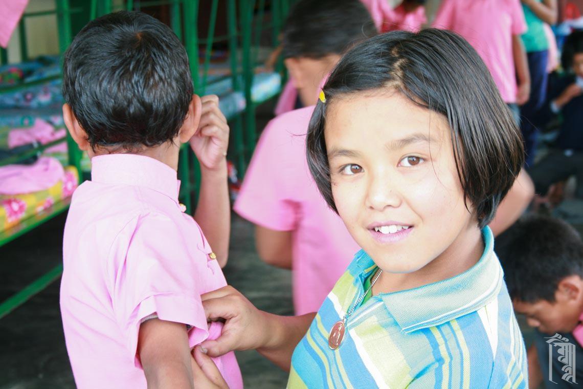 Ältere Kinder helfen jüngeren Kindern, sich jeden Tag auf die Schule vorzubereiten.