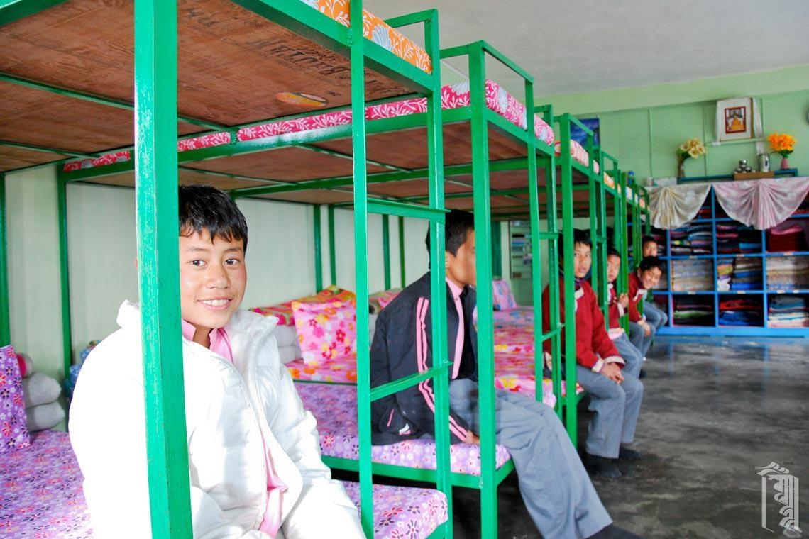 Die Kinder sitzen auf frisch gemachten Betten in einem sauberen Familienhaus.