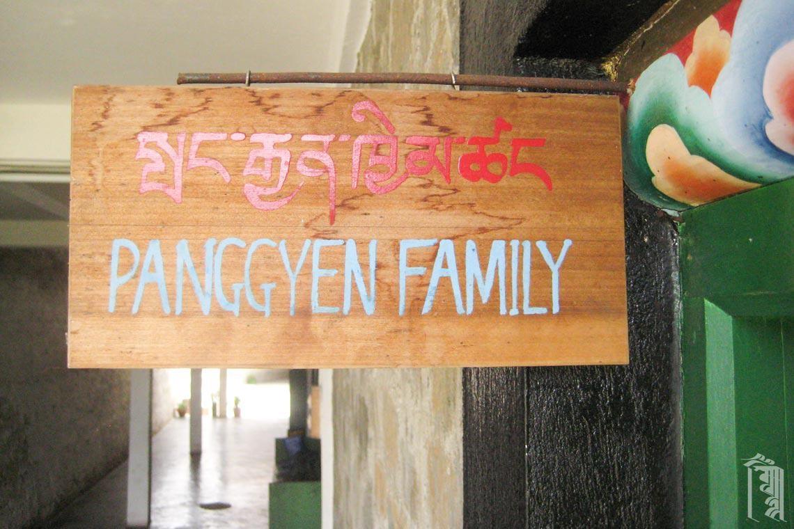 Ein hölzernes Schild vor einem der Jhamtse Gatsal Familienhäuser.