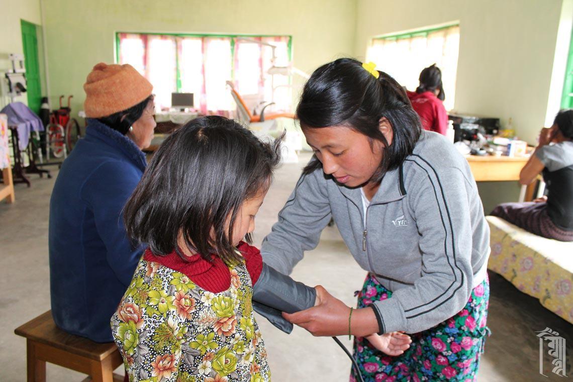 Eine Schülerin lernt in der Klinik mit Unterstützung des Gastarztes Dr. Vindy, wenn Besucher aus dem Dorf zu einer Untersuchung kommen.