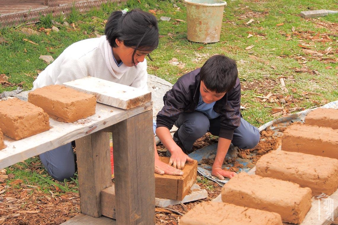 Diese Schüler helfen bei der Herstellung von Ziegelsteinen aus Ton, der in einem nahegelegenen Dorf ausgegraben wurde. Es ist Teil eines Lehmofenprojekts mit einem Freiwilligen.