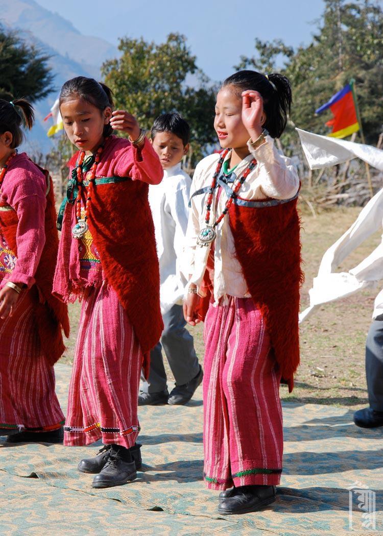 Junge Schüler im Jhamtse Gatsal, die vor besonderen Gästen in traditioneller Monpa-Kleidung auftreten.
