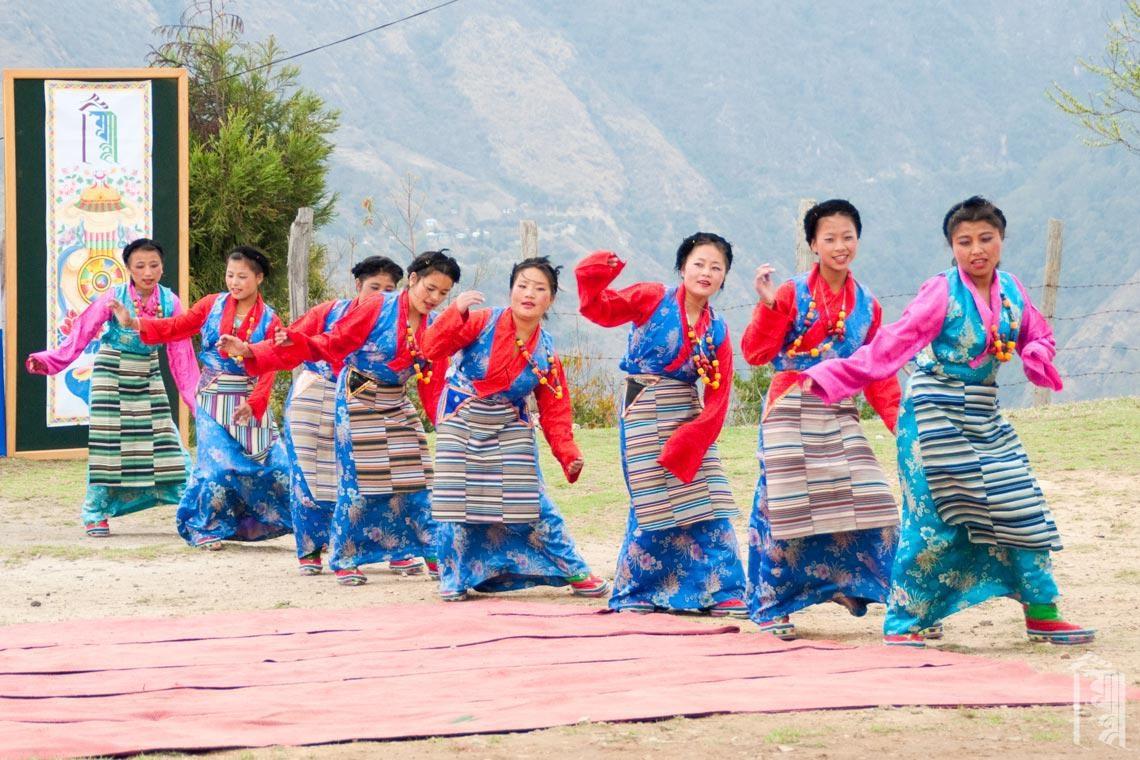 Bunte Tanzkostüme erhellen selbst einen wolkenverhangenen Tag auf dem Jhamtse Gatsal Children's Community Höhenzug.
