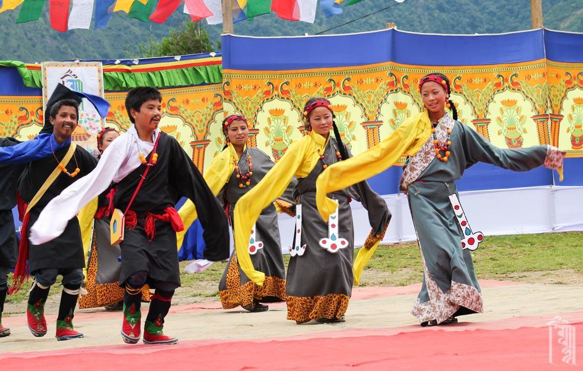 Trachten und ein farbenfroher Hintergrund machen Tanzaufführungen im Jhamtse Gatsal zu einem sehenswerten Ort.