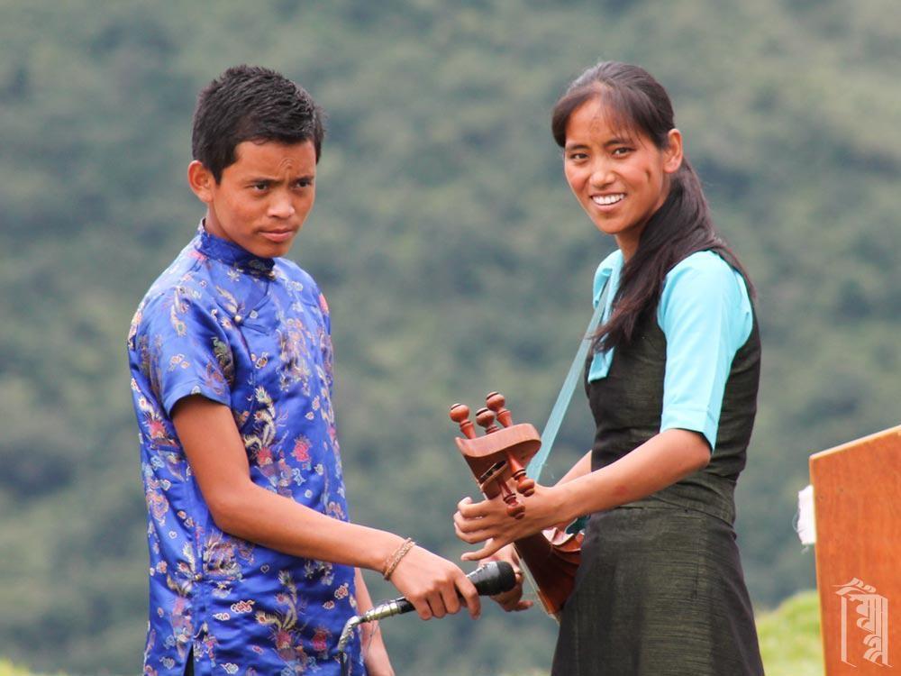Unsere tibetische Musik- und Tanzlehrerin Yangkyi begleitet einen Tanz auf ihrem Dranyen (Tibetische Gitarre).