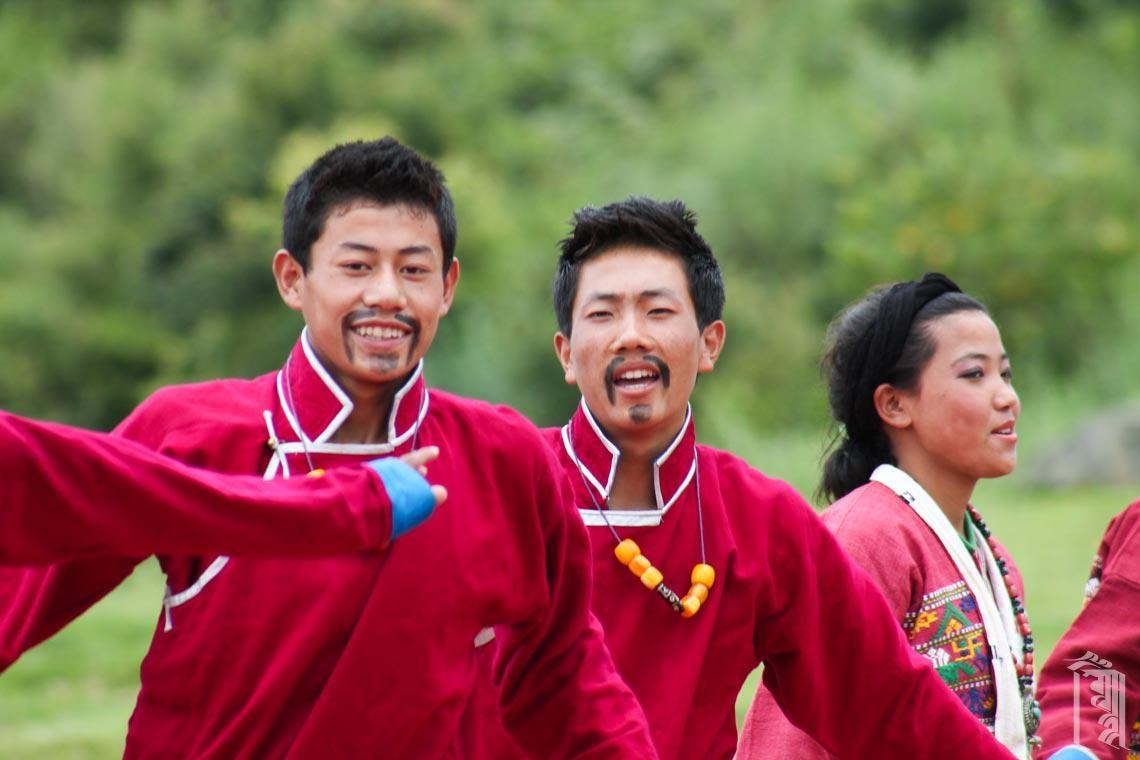Zu den speziellen Kleidungsstücken für Monpa-Jungen gehört eine feierliche rote oder schwarze Jacke, die hier für eine Tanzperformance getragen wird.