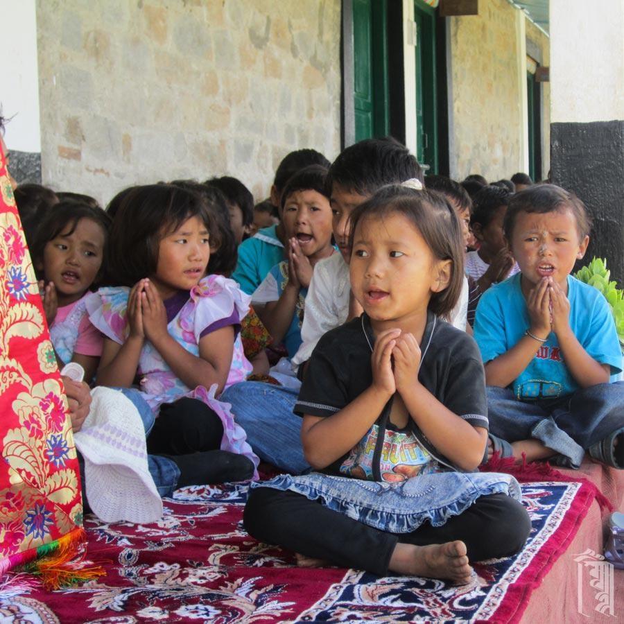 Kinder jeden Alters nehmen am Sprechgesang teil, wenn Jhamtse Gatsal ein Gemeinschaftsgebet hält.