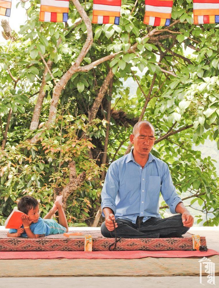 Der Leiter der Gemeinschaft, Lobsang Phuntsok, leitet die Mitarbeiter und Kinder in buddhistischen Gebeten bei einem wichtigen Anlass.