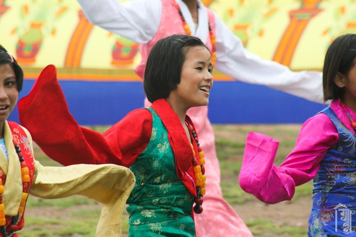 Die Schüler der 5. Klasse in bunten tibetischen Chupas lachen, während sie einen traditionellen Tanz aufführen.