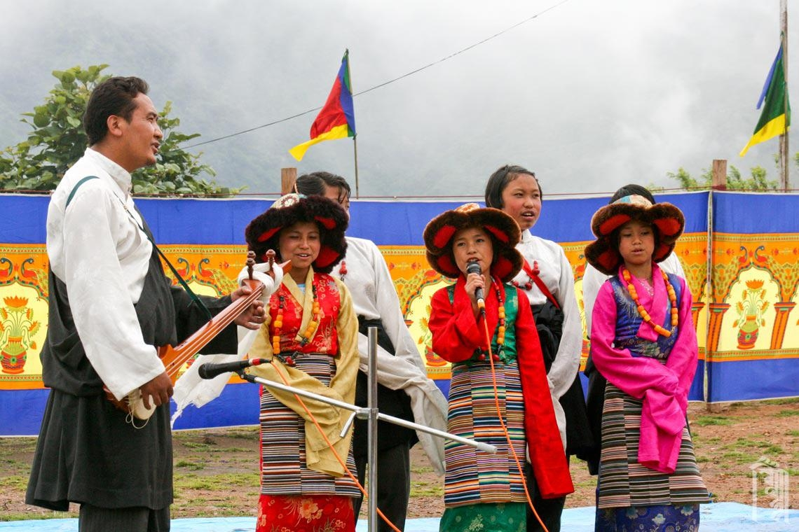 Der Bhoti-Lehrer Gen Sangpo begleitet eine Gruppe von Kindern bei der Aufführung eines traditionellen tibetischen Liedes.