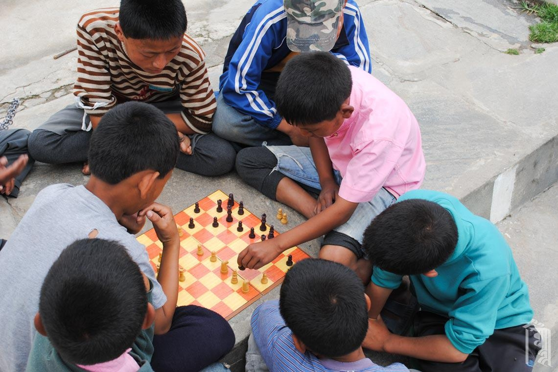 Eine ganze Gruppe von Jungen aus der Mittelstufe vergnügen sich still und leise mit einer Schachpartie.