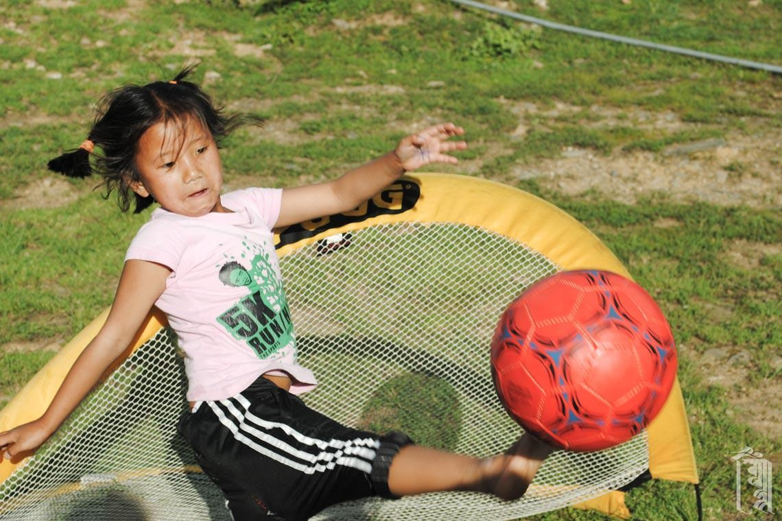 Eines der jüngsten Mitglieder der Community lernt Fußball spielen und macht einen Satz beim Hüten des kleinen Tores.