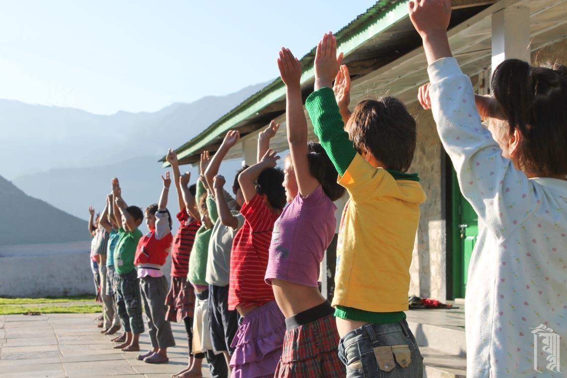 Kinder nehmen an Yoga oder anderen Übungen als Teil ihres täglichen Morgenprogramms teil.
