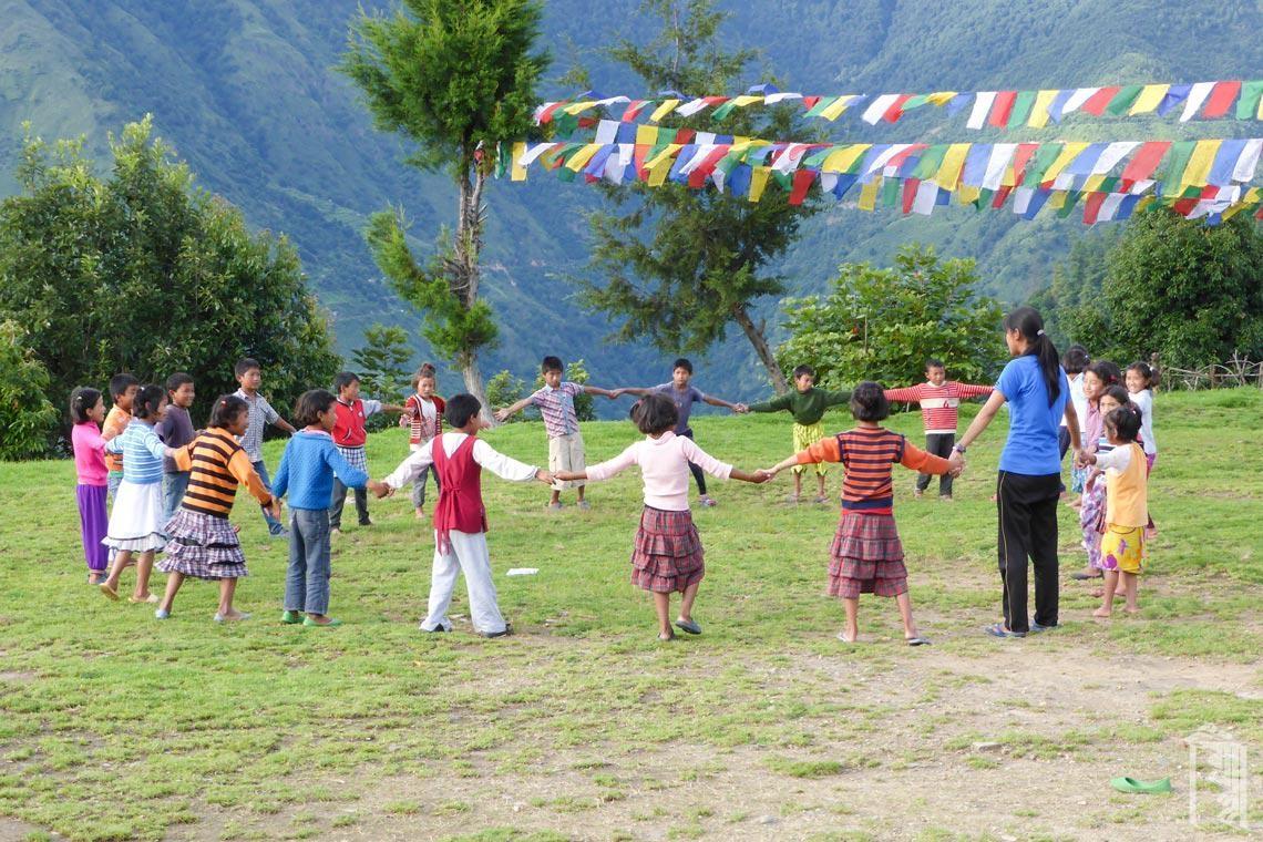 Eine Gruppe der jüngeren Schüler lernt einen traditionellen Tanz mit der Musik- und Tanzlehrerin Ma'am Yangkyi.