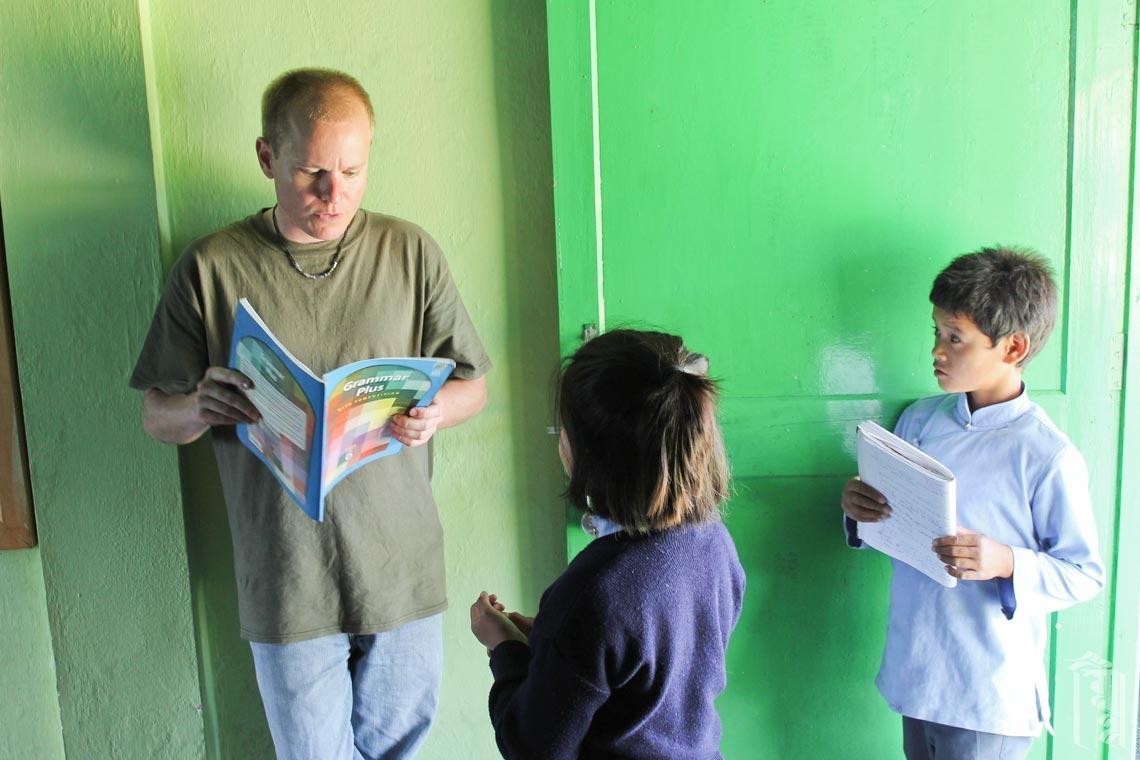 Der freiwillige Lehrer Adam Johnson hilft Schülern zwischen den Unterrichtsstunden am Jhamtse Gatsal.