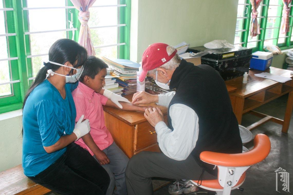 Der medizinische Freiwillige Dr. Craig Ottenstein führt mit Hilfe der Hausmutter Tenzin Choikey Untersuchungen an den Kindern durch.