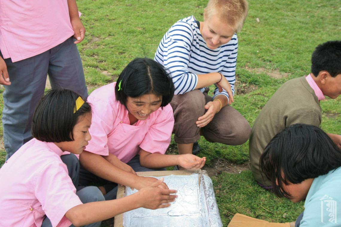 Eine JGCC Freiwillige arbeitet mit einigen der Kinder an einem experimentellen Solarofenprojekt.