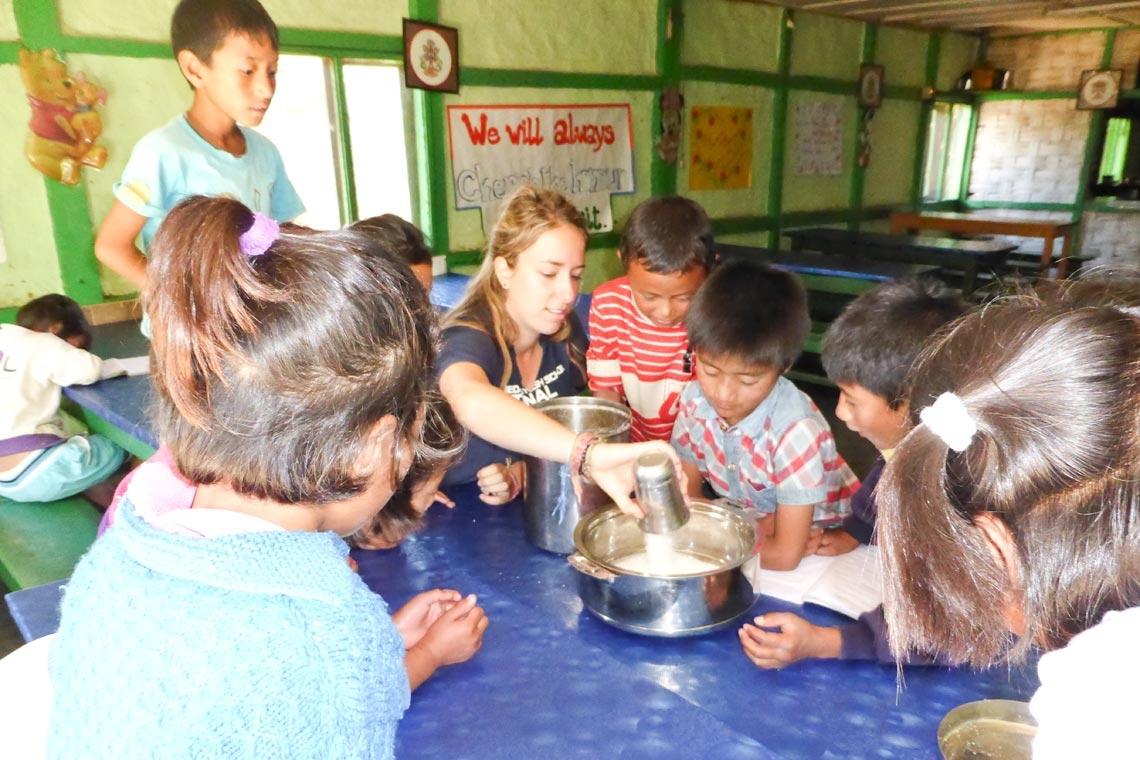 Freiwillige Emma Currier hat Spaß mit einer Gruppe jüngerer Schüler, die ein Kochprojekt in der Küche des Jhamtse Gatsal durchführen.