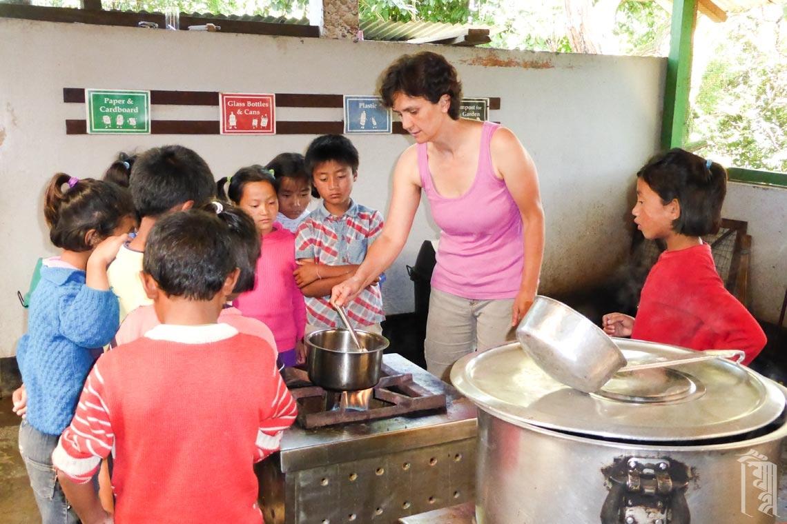 Die Freiwillige Mira Lucic unterrichtet eine Gruppe von Schülern, wie man in der Küche von Jhamtse Gatsal ein besonderes Dessert zubereitet.