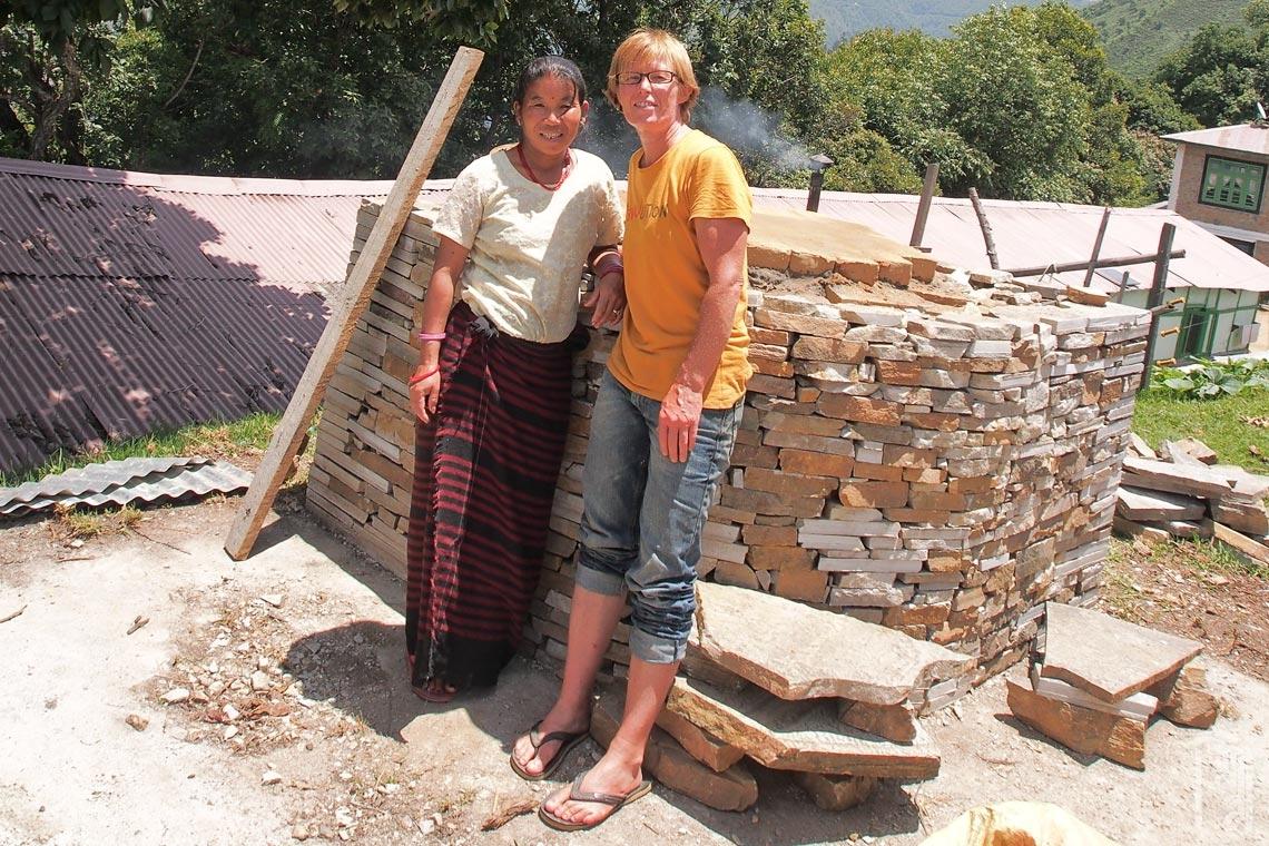 Freiwillige natürliche Bauherrin und Bäckerin, Kate Eldridge, arbeitet hart an einem holzgefeuerten Lehmofen, den sie bei der JGCC-Küche baut.