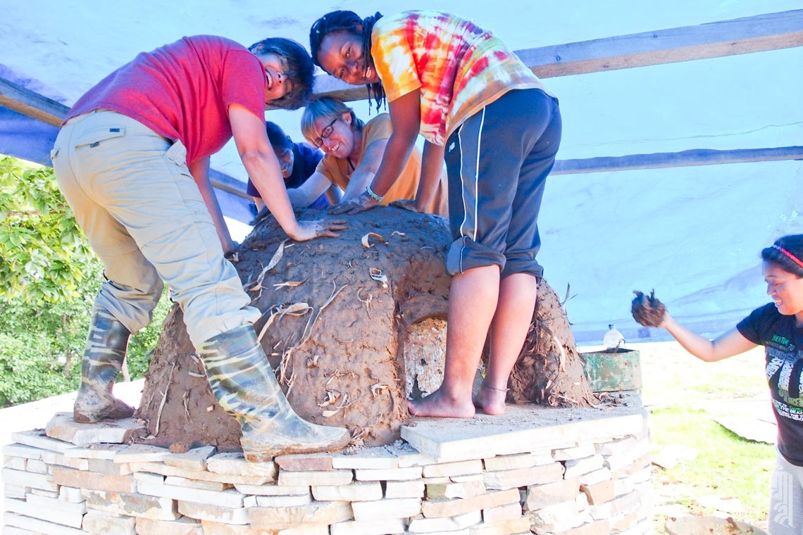 Vasudha Wanchoo und die Freiwilligen Kate Eldridge und Amma Spence sowie der JGCC-Lehrer Gombu Lhamu bauen gerne gemeinsam einen Lehmofen.