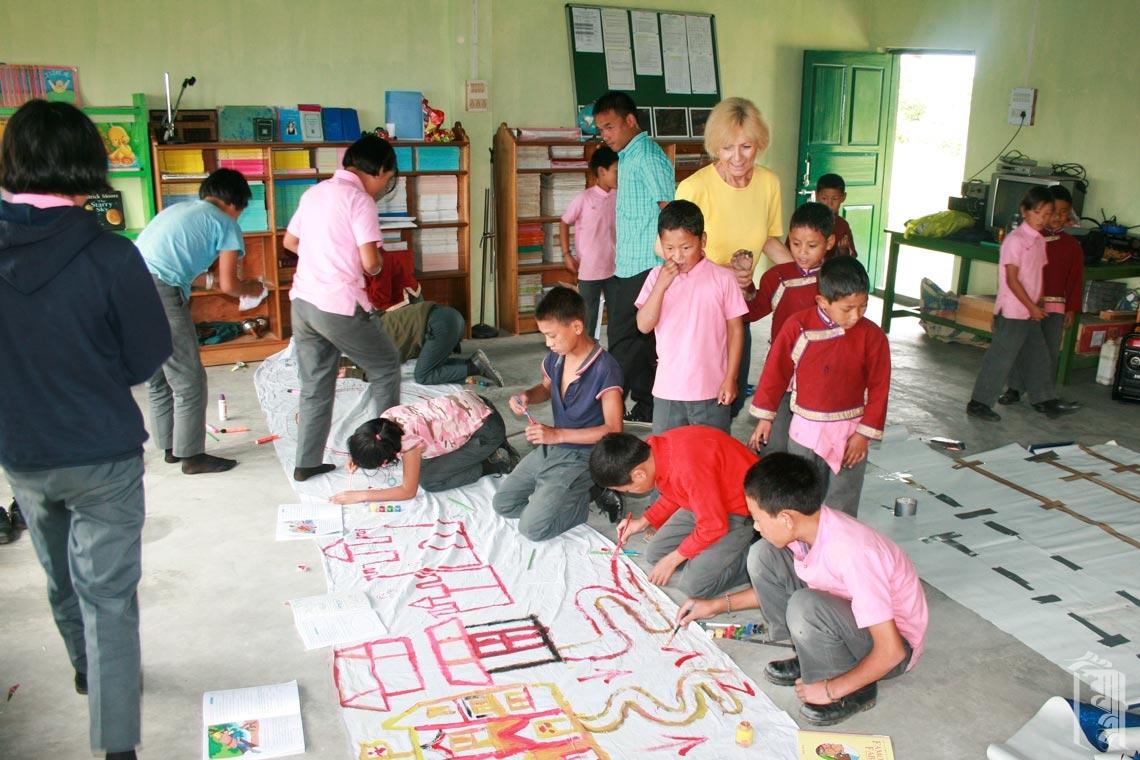 Die ehrenamtliche Theaterpädagogin Suzanne Bader arbeitet mit den Schülern zusammen, um Sets für eine bevorstehende Theaterproduktion am Jhamtse Gatsal zu erstellen.