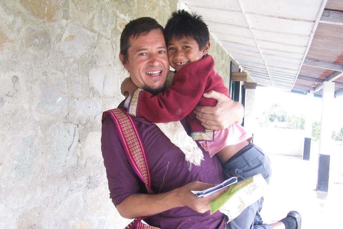 Ein ehrenamtlicher Künstler aus Argentinien hängt mit den Kindern zwischen den Malprojekten zusammen.