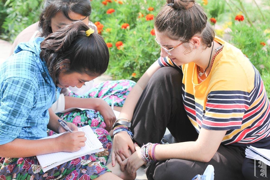 Die ehrenamtliche Betreuerin Sara hilft den Schülern bei ihren Hausaufgaben am Nachmittag.